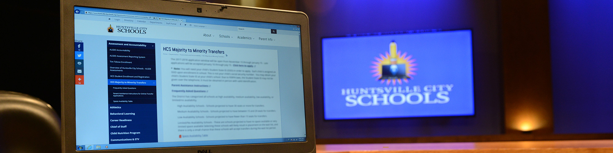 Laptop computer on the district website M2M Application page, with a blue HCS Logo (blurred) in the background